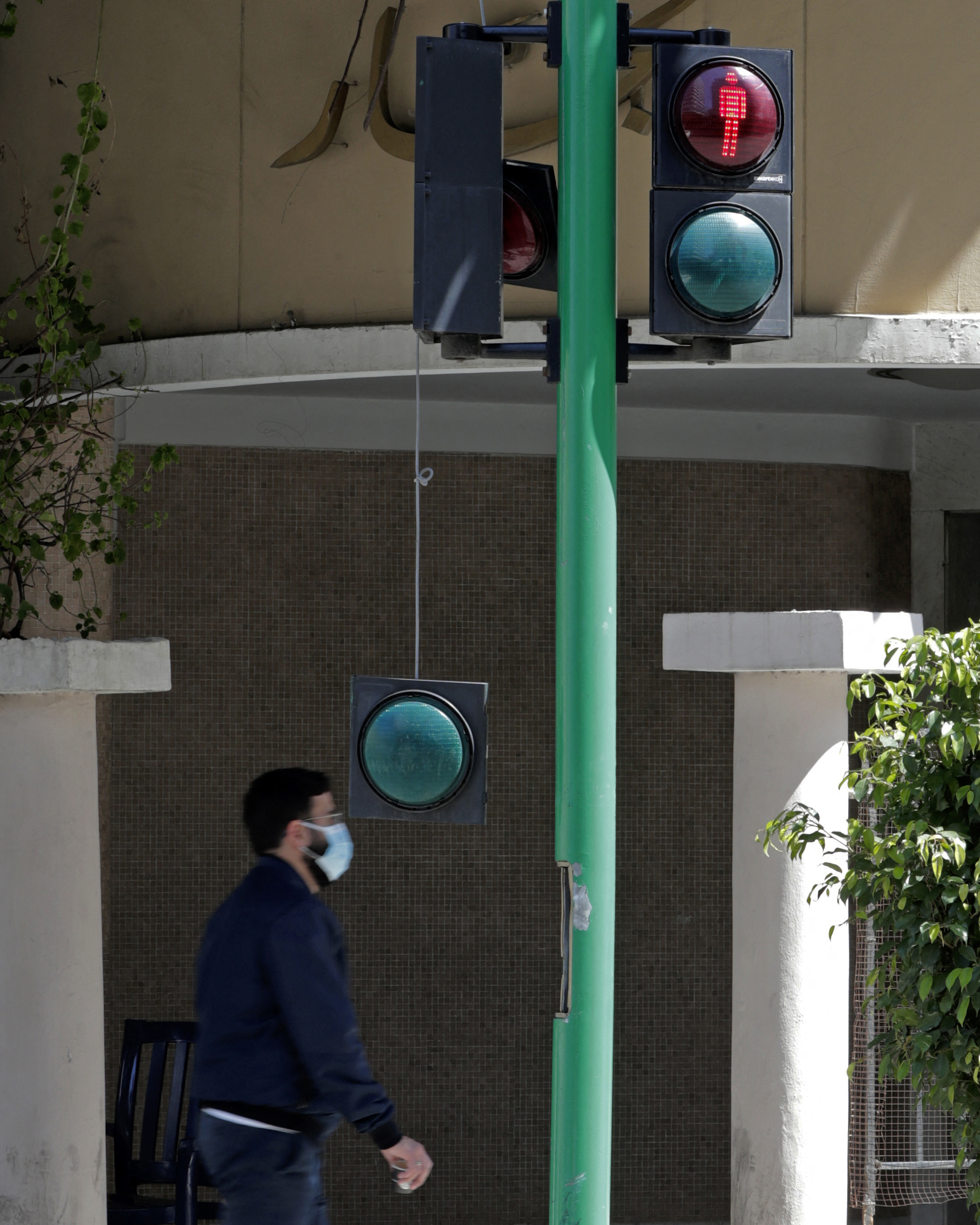 A man walks behind a broken traffic light in the Lebanese capital Beirut on March 31, 2021. - As Lebanon battles its worst…