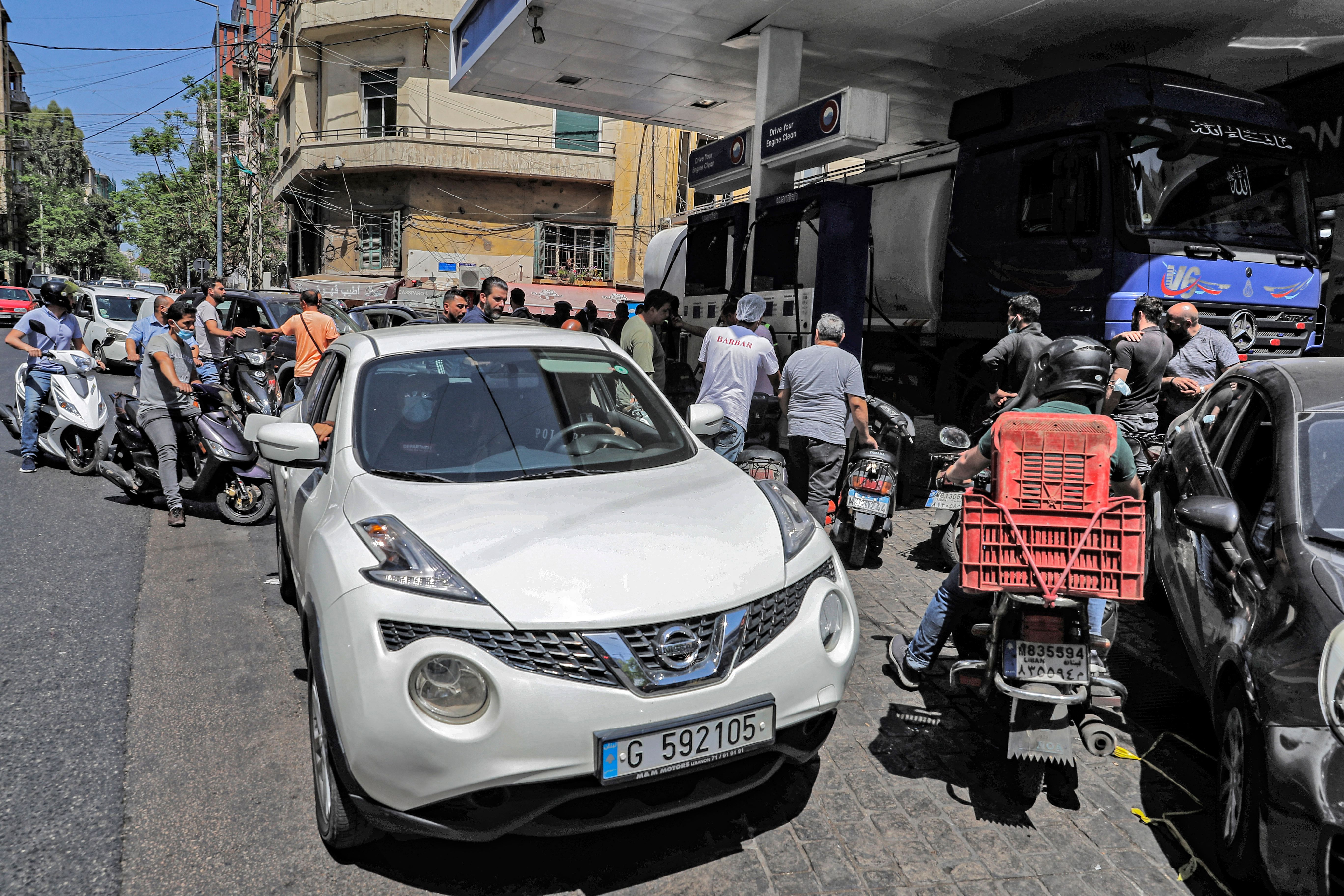 Vehicles queue-up for fuel at a petrol station in Lebanon's capital Beirut on June 11, 2021 amidst severe fuel shortages. - The…