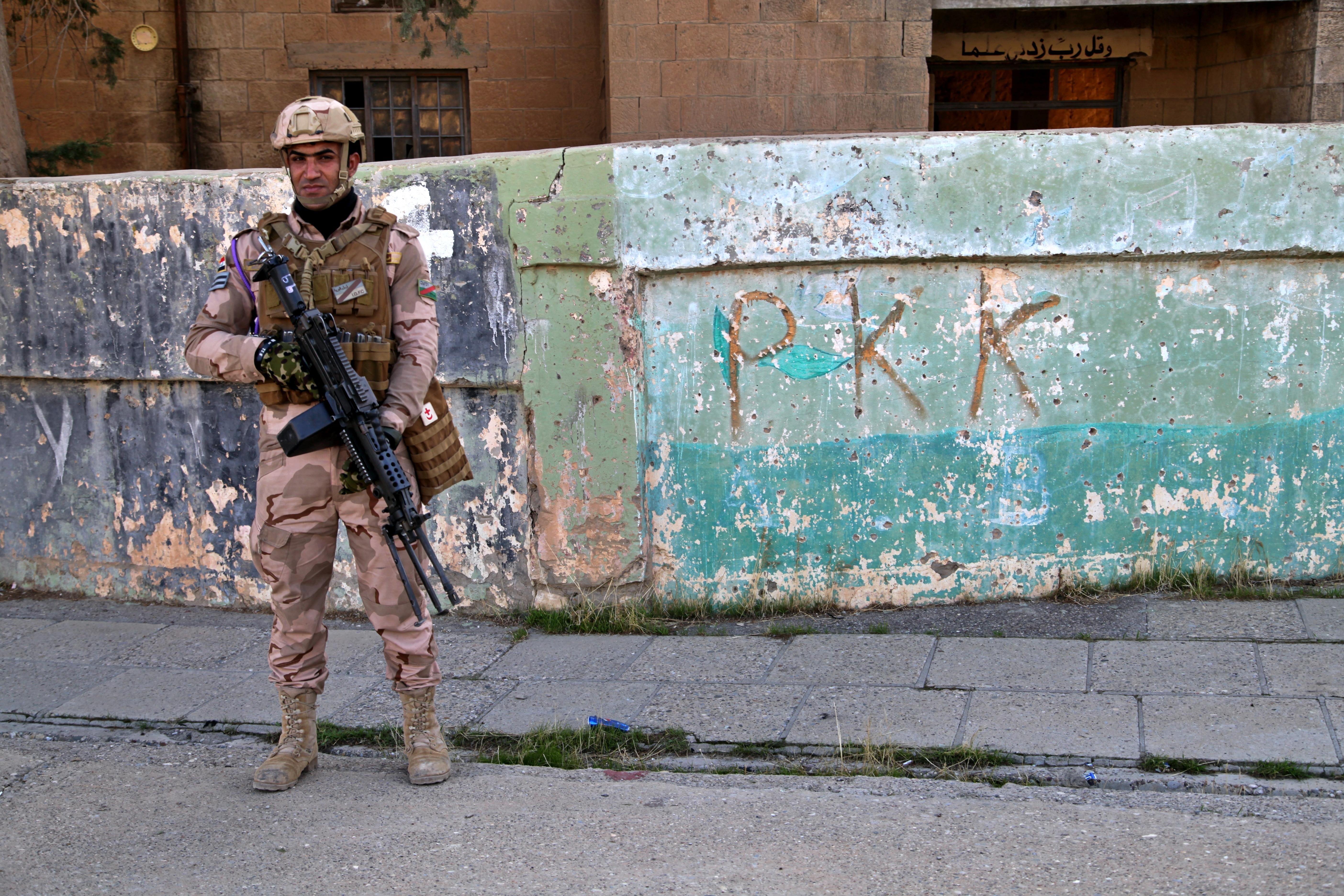 חייל צבאי עירקי עומד ליד הגרפיטי שהשאיר שלוחה של מפלגת העובדים בכורדיסטאן, או PKK, אשר לאחרונה ...