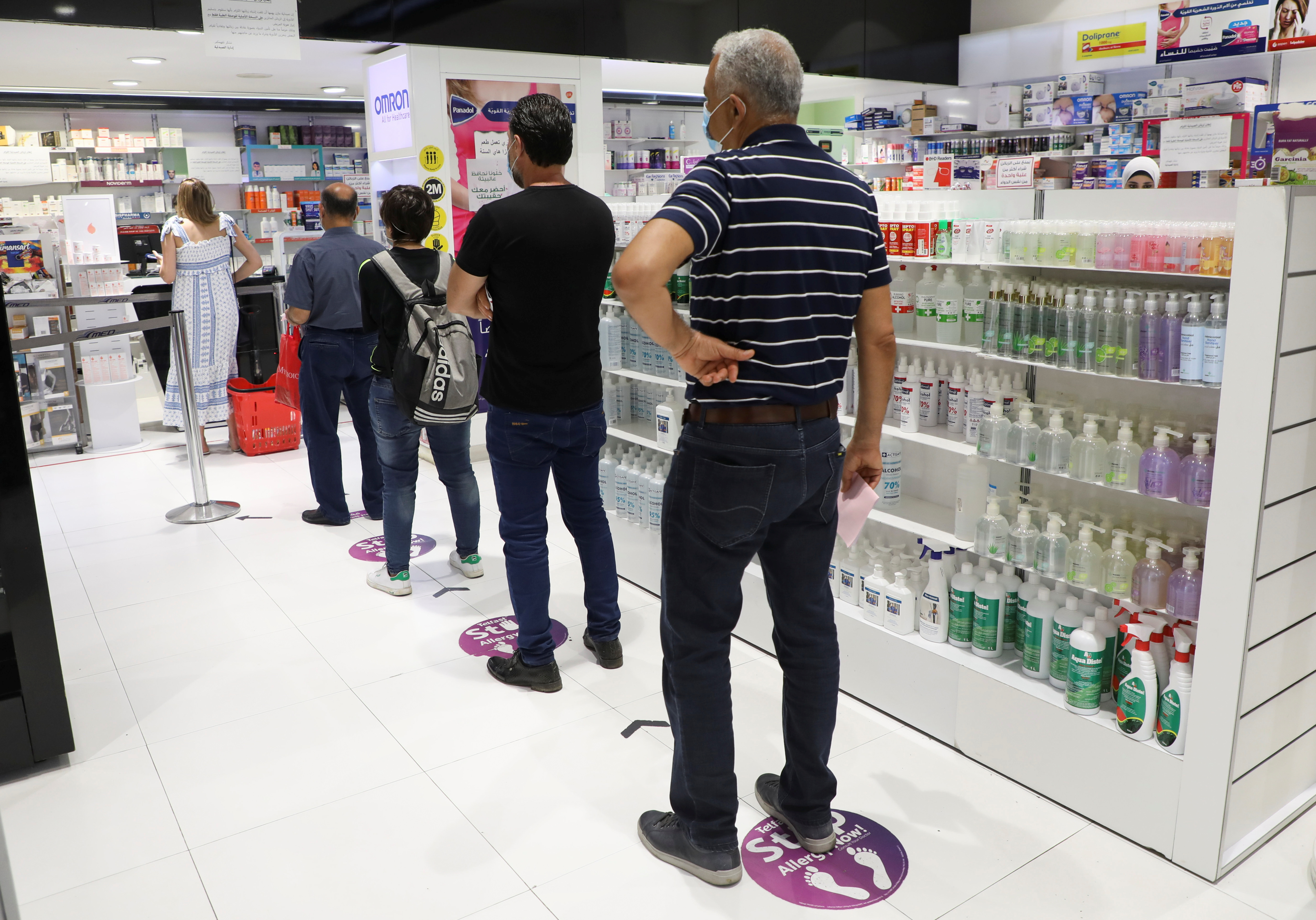 People queue inside a pharmacy in Beirut