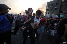 متظاهر يحمل جريحا خلال احتجاجات العراق