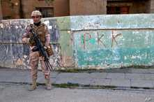 Iraqi army soldier stands next to the graffiti left by an affiliate of the Kurdistan Worker's Party, or PKK, which recently…