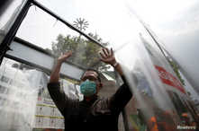 A man wearing face mask is sprayed inside a disinfection chamber, outside a shopping mall after Indonesia's capital begins a…