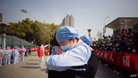 A medical worker (R) embraces a member of a medical assistance team from Jiangsu province at a ceremony marking their departure…