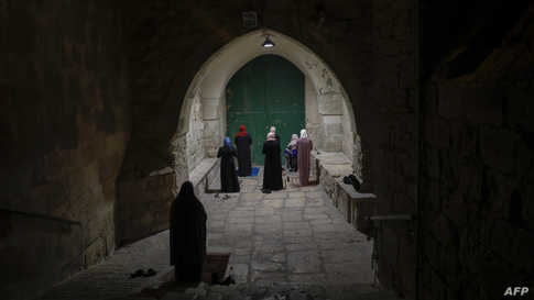 Palestinian Muslim women worshippers, distanced from each other due to the COVID-19 coronavirus pandemic, pray outside the…