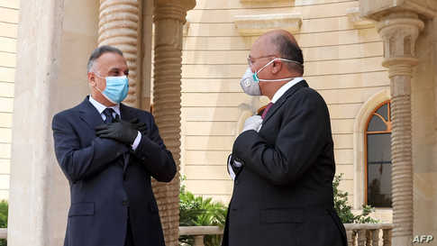This handout photograph released by the Iraqi President's Office on May 28, 2020 shows President Barham Salih (R) receiving…