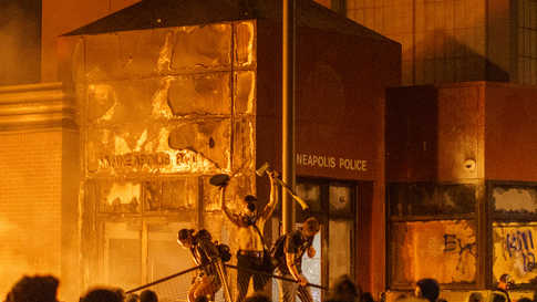 Flames from a nearby fire illuminate protesters standing on a  barricade in front of the Third Police Precinct on May 28, 2020…