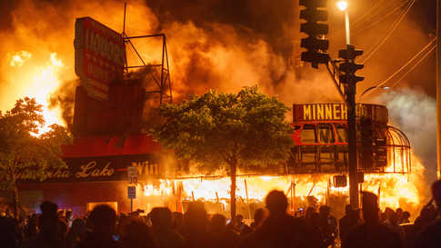 Protesters gather in front of a liquor store in flames near the Third Police Precinct on May 28, 2020 in Minneapolis, Minnesota…