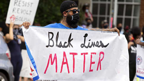 A man holds a Black Lives Matter banner during a racial justice protest in Charlottesville on May 30, 2020. - Demonstrations…