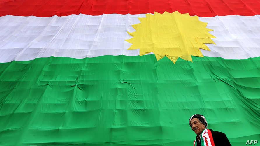 مواطن كردي يمر عند علم كردستان في يوم العلم