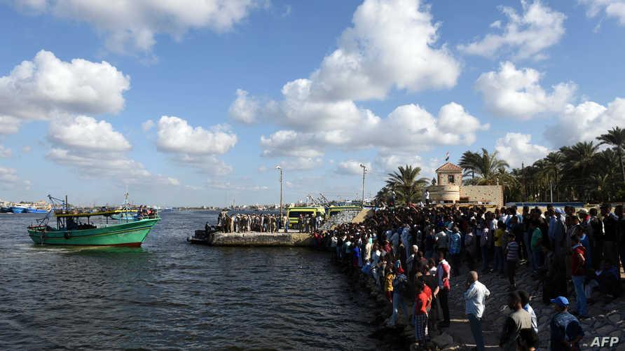 مصريون على الشاطئ في انتظار انتشال جثث ضحايا قارب المهاجرين الذي غرق قبالة مدينة رشيد
