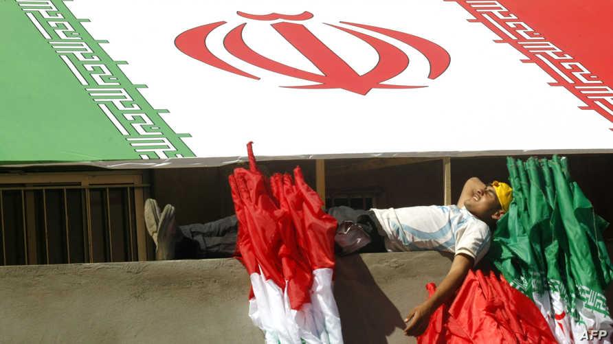 عامل يستريح تحت علم إيران في جنوب لبنان - أرشيف