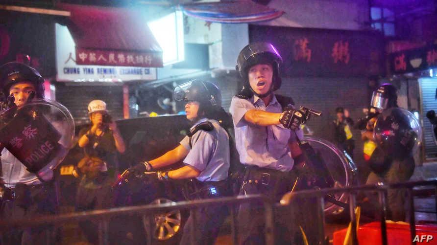 ضابط شرطة يوجه سلاحه ناحية المتظاهرين في تسوين وان في هونغ كونغ