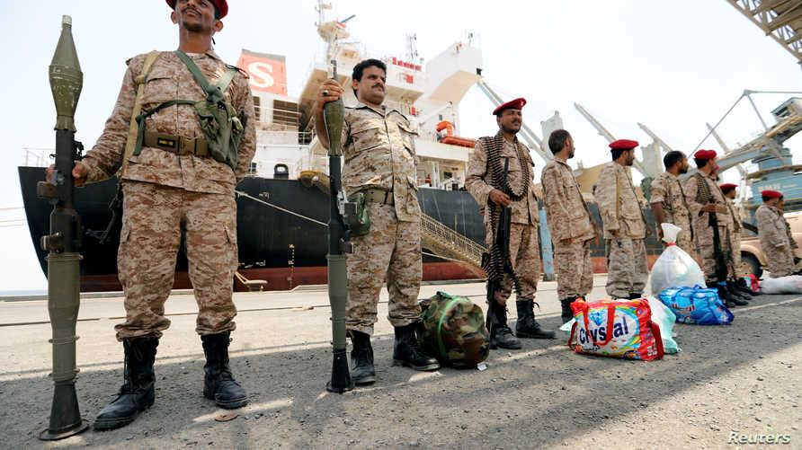 عناصر في القوات التابعة للحوثيين خلال الانسحاب من ميناء الصليف في الحديدة