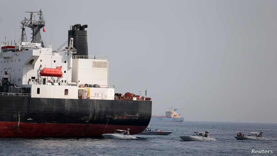 زوارق تابعة للبحرية الإماراتية قرب ناقلة النفط السعودية التي تعرضت لأضرار إثر استهدافها في ميناء الفجيرة