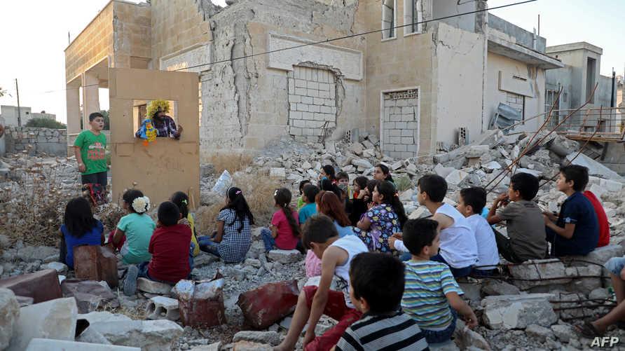 وليد أبو راشد على رأسه باروكة المهرج وحوله عشرات الأطفال المتلهفين لمشاهدة عرضه المسرحي الجديد