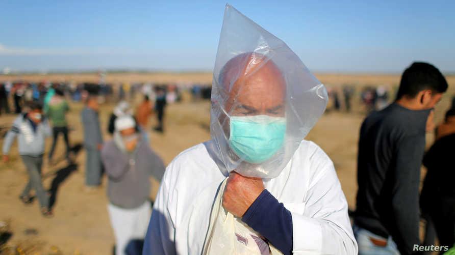 متظاهر فلسطيني يرتدي كيسا من البلاستيك كقناع يقيه من الغاز المسيل للدموع شرق غزة