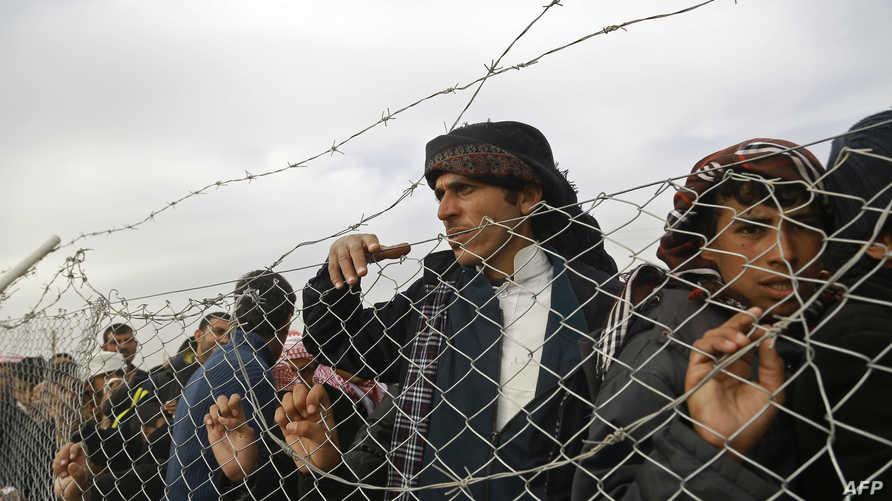 لاجئون قرب سياج مخيم الهول في الحسكة