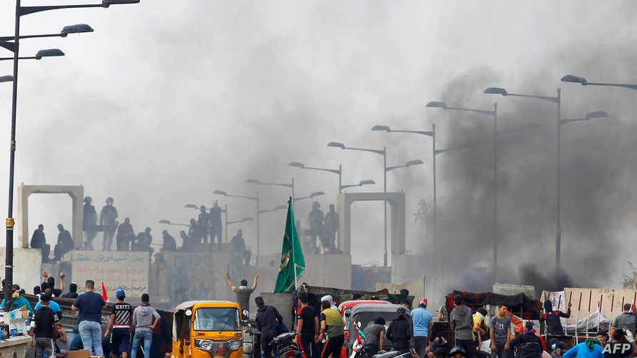 تظاهرة في بغداد بينما تقف الشرطة العراقية على جسر الجمهورية- 27 أكتوبر 2019