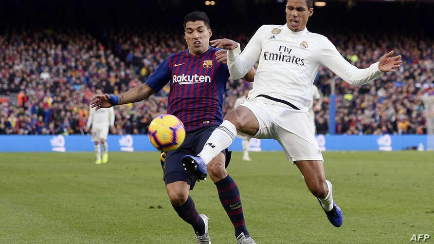 صراع على الكرة بين مهاجم برشلونة لويس سواريز ومدافع ريال مدريد رافائيل فاران في آخر مباراة بينهما في أكتوبر الماضي