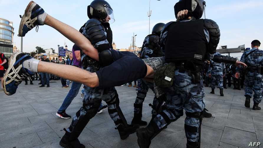عناصر في الشرطة الروسية خلال اعتقال أحد المتظاهرين في موسكو