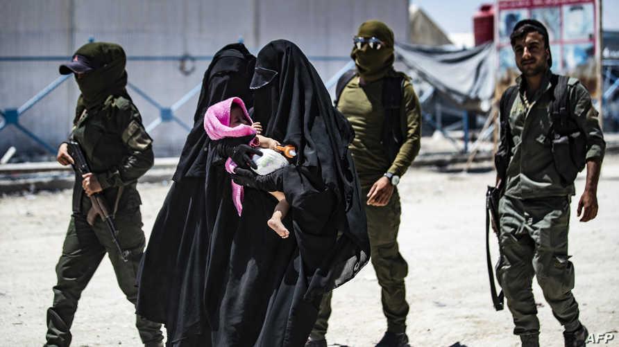 عناصر أمنية كردية في مخيم الهول ترافق نساء من أقارب عناصر داعش