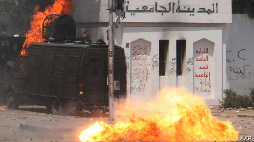 سيارة شرطة مصرية تحترق بعد اشتباكات مع مناصري الإخوان المسلمين (أرشيف)