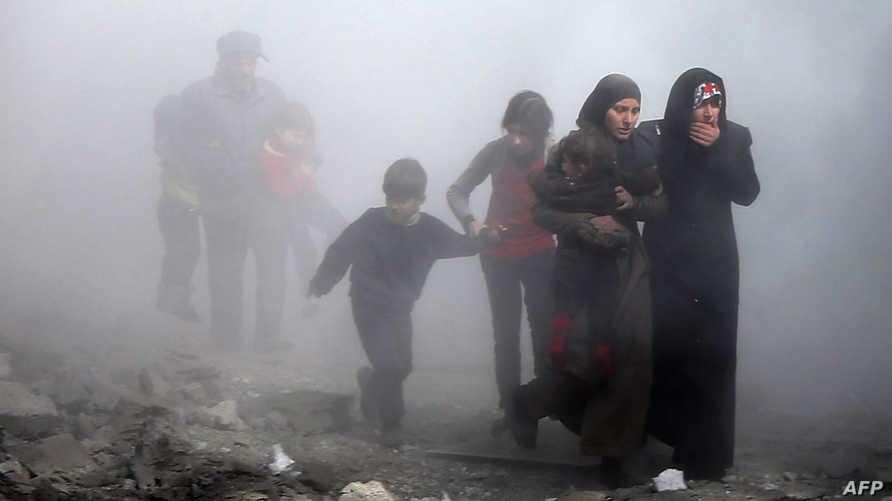 مدنيون يفرون من إحدى المناطق التي تعرضت للقصف في الغوطة الشرقية في الثامن من فبراير 2018