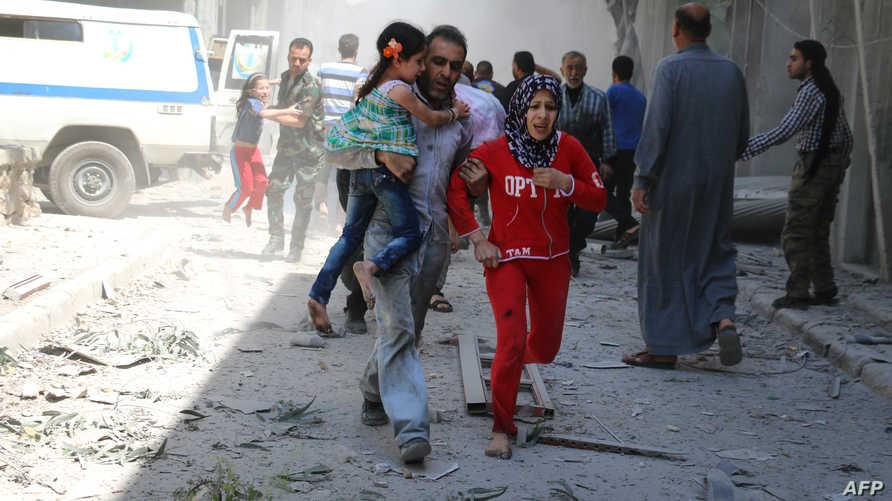 عائلة سورية تفر بعد غارة جوية على حلب_أرشيف.