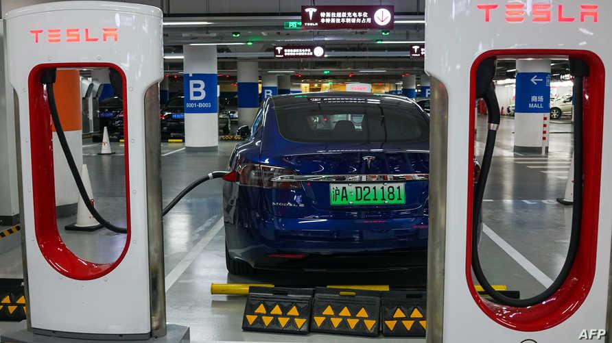 سيارة تسلا في محطة تعبئة كهربائية