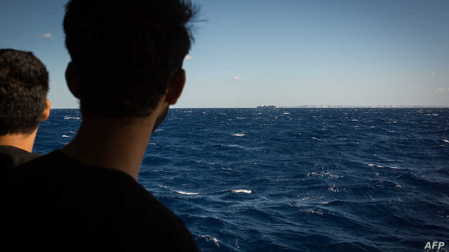 مهاجرون ينظرون إلى الساحل بعد أن أنقذتهم سفينة أكواريوس في سبتمبر الماضي