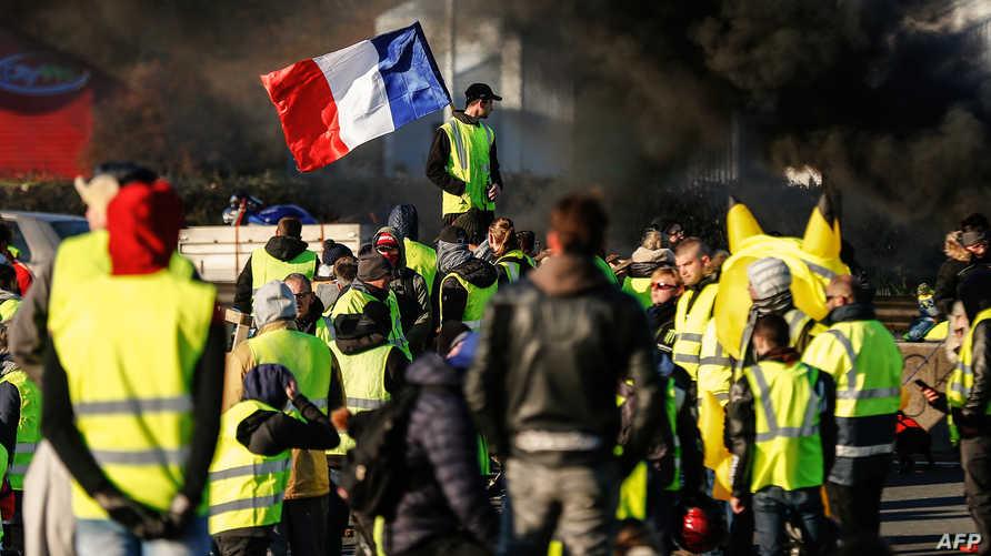 مجموعة من متظاهري السترات الصفراء يرفعون العلم الفرنسي