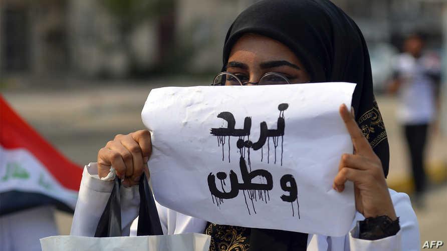 """طالبة طب ترفع لافتة تقول: """"نريد وطن"""" خلال التظاهرات المعارضة للحكومة"""