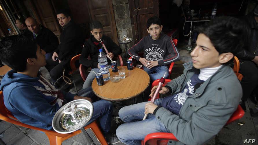 أطفال سوريون يدخنون النرجيلة في أحد مقاهي دمشق- أرشيف