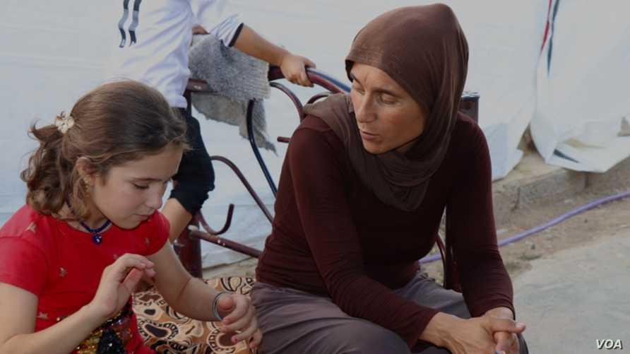 فادية بجانب أمها حيث عادلت لعائلتها بعد أن كانت مستعبدة من قبل عناصر داعش