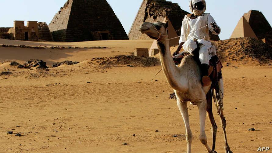 """سوداني يمتطي جملا بالقرب من أهرامات بنيت في عهد مملكة """"كوش"""" في صحراء مروي في السودان"""