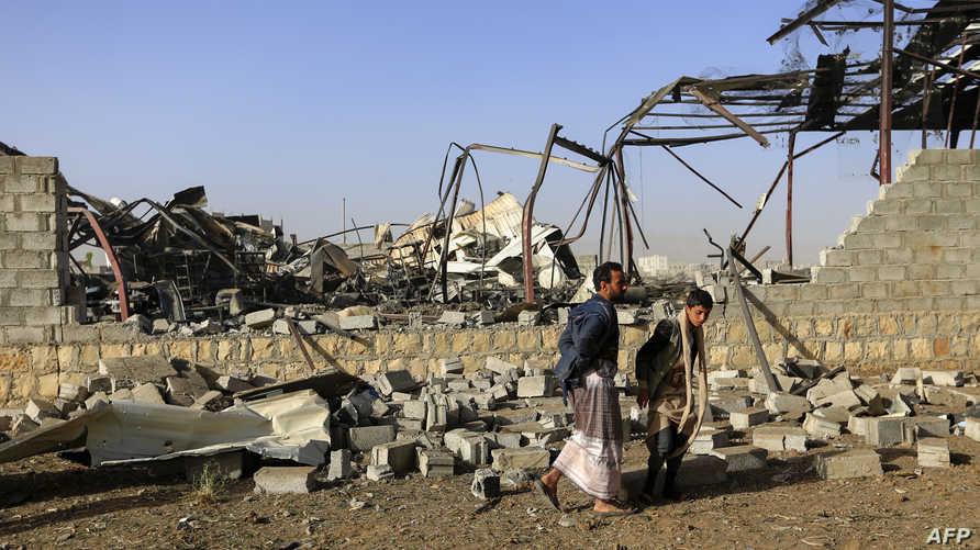 يمنيون يتفقدون أضرارا في موقع بالعاصمة صنعاء بعد ضربة جوية للتحالف بقيادة السعودية
