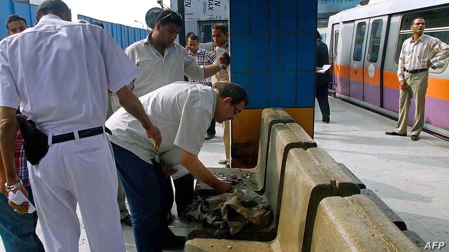 أفراد من الشرطة المصرية يفحصون موقع تفجير استهدف محطة مترو شبرا الخيمة