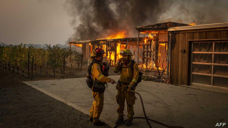 رجل أطفاء يعملون على إخماد حريق شب في منزل في هيلدزبيرغ بولاية كاليفورنيا بتاريخ 27 أكتوبر 2019