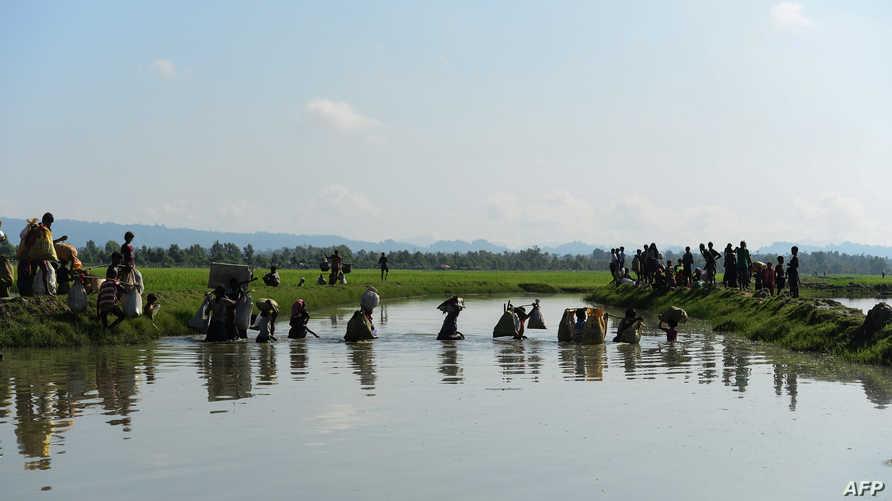 أفراد من الروهينغا يعبرون إلى بنغلادش هربا من العنف في راخين