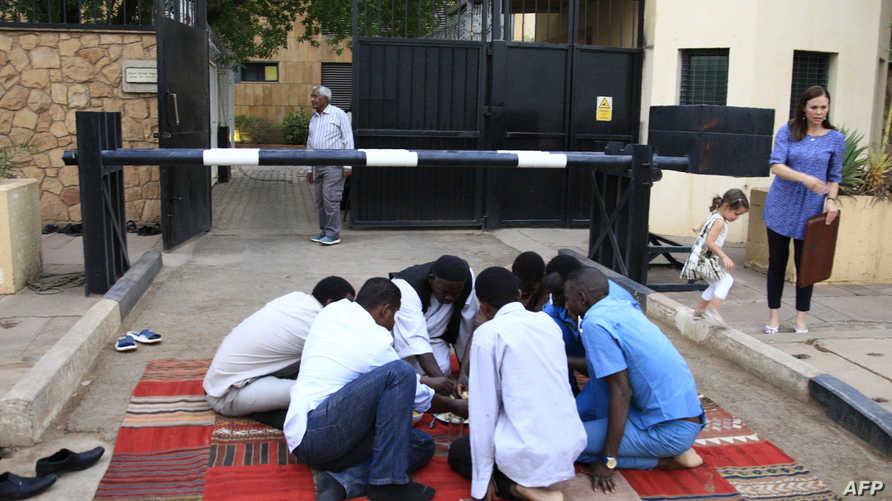 سودانيون معتصمون أمام مقر إقامة السفير البريطاني في العاصمة الخرطوم يتناولون الإفطار في رمضان