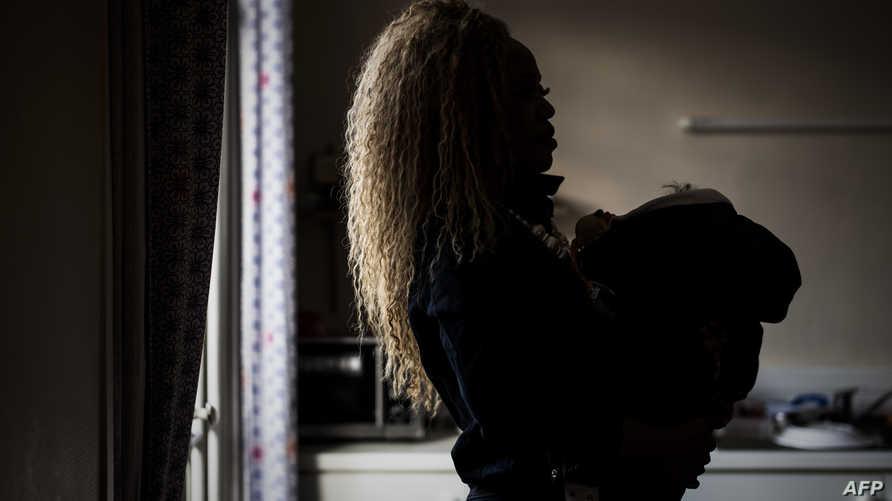 سيدة مصابة بالإيدز تحمل طفلها في إحدى العيادات