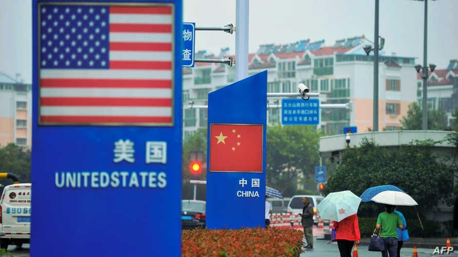 العلم الأميركي والعلم الصيني خارج متجر لبيع البضائع المستوردة شرق الصين