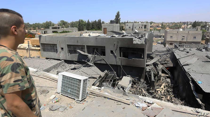 مقاتل في القوات الموالية لحكومة الوفاق في غرب ليبيا يفحص أضرارا لحقت بمبنى جراء قصف القوات الموالية لحفتر