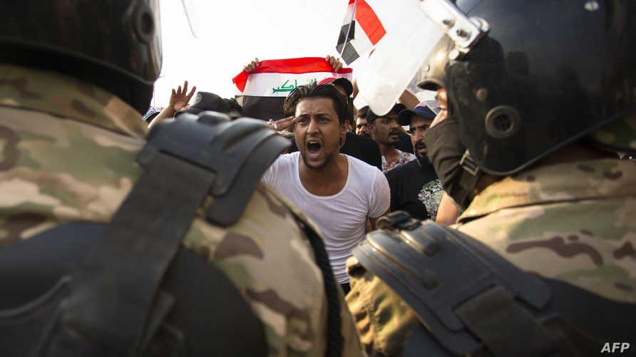 متظاهر في مواجهة قوات الأمن العراقية في البصرة