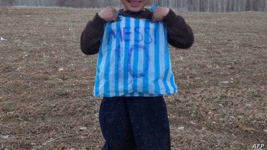 الطفل الأفغاني مرتضى أحمدي يحمل قميصا بلاستيكيا للاعب ميسي