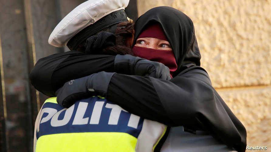 سيدة منقبة تبكي خلال احتضانها شرطية دنماركية خلال تظاهرة ضد قانون حظر النقاب في الدنمارك