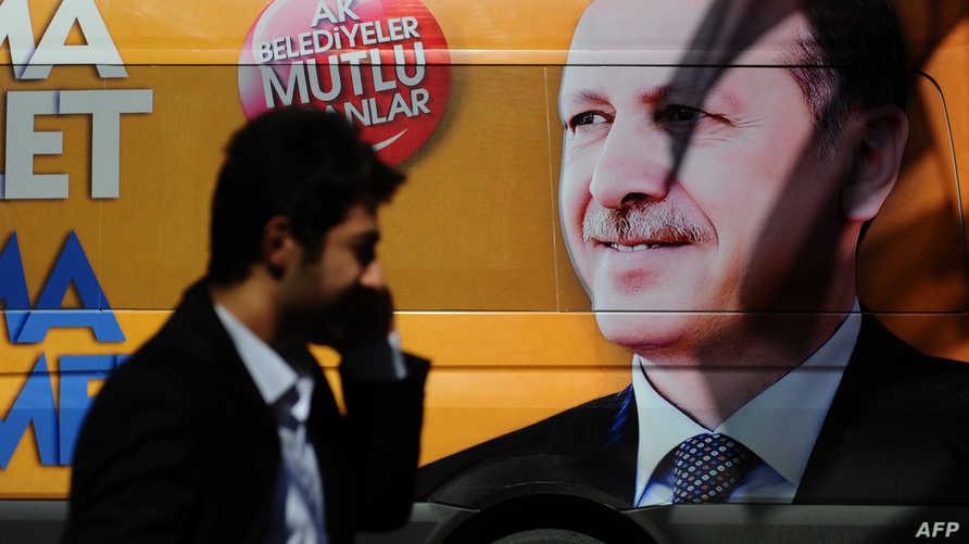 شاب تركي يمر بجانب حافلة عليها صورة أردوغان - أرشيف