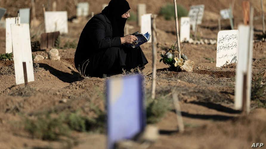 أم سورية تتلو آيات من القرآن عند قبر ابنها الذي قتل في الحرب الجارية