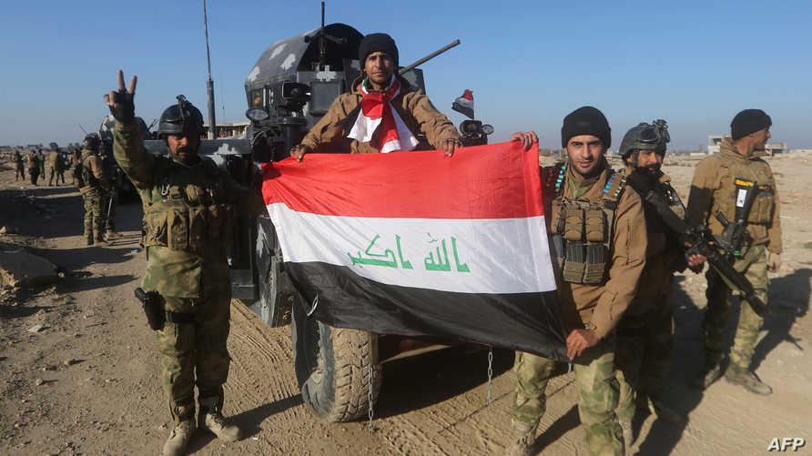 منتسبون في جهاز مكافحة الإرهاب يحملون العلم العراقي في الرمادي
